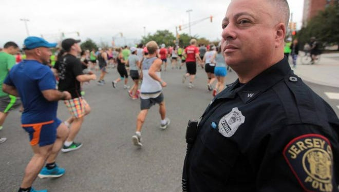 Jersey City Police Officer Frank Scarpa keeps a watchful eye on runners near the start of the Newport Half Marathon in Jersey City, N.J., Sept. 18, 2016.
