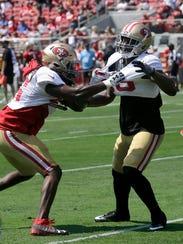 San Francisco 49ers' Jayson DiManche, left, grabs the