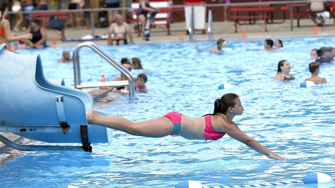 Kaelyn Weaver goes head first into the pool from one of the slides at Brookside Pool on Wednesday.