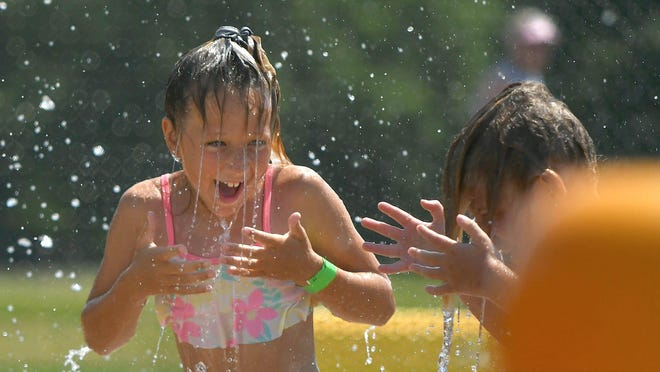 Fourth-grader Jacalyn Lehman cools off at the Dogwood Pool spray park on Thursday. The pool reopened, with COVID-19 restrictions, on Wednesday, just in time for a hot Independence Day holiday weekend.