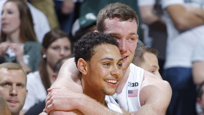 Seniors Bryn Forbes, left, and Matt Costello watch from the bench during the closing moments of the victory over  Ohio State on Saturday.
