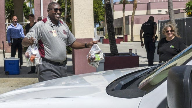 Lake Worth High School principal Elvis Epps carries free breakfasts and lunches to a parent at the school on March 16.