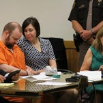 Joshua Burns, in orange, and wife Brenda Burns hold hands in this file photo from a July hearing where he learned he will not lose his parental rights to his daughter. Also pictured is Brenda Burns' attorney, Elizabeth Warner, far right.