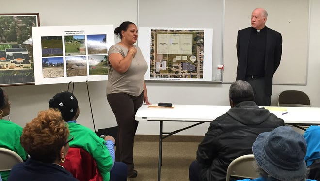 Kim Tandy, District 2 manager for the Detroit mayor's office, and Rev. Theodore Munz, president of U of D Jesuit High School and Academy, speak to residents at a community meeting about the school's plans to redevelop the Johnson Recreation Center. The meeting was held March 23, 2017 at New Prospect Baptist Church.