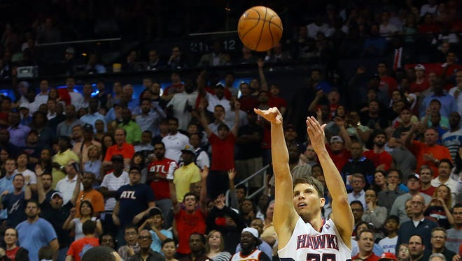 The Atlanta Hawks' Kyle Korver hits a 3-point shot over the Indiana Pacers' George Hill late in the second half of Game 3 in an Eastern Conference quarterfinal on Thursday, April 24, 2014, at Philips Arena in Atlanta.