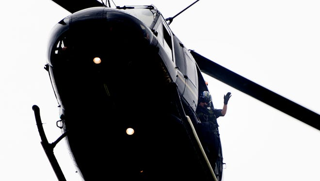 A member of the Knox County Sheriff's department waves from a helicopter overhead during the annual Powell Fourth of July Parade in Powell, Tennessee on Tuesday, July 4, 2017.