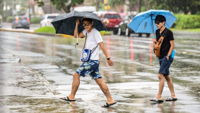 Two men rush across San Vitores Road during a downpour in Tumon on Tuesday, Oct. 17, 2017.