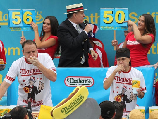 Joey Chestnut, left, and Matt Stonie compete in Nathan's Famous Fourth of July International Hot Dog Eating Contest men's competition Saturday July 4, 2015, in the Coney Island section in the Brooklyn borough of New York. Stonie came in first eating 62 hot dogs and buns in 10 minutes. Chestnut came in second eating 60 hot dogs and buns in 10 minutes.