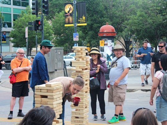 A giant Jenga set draws a crowd on South Dubuque Street