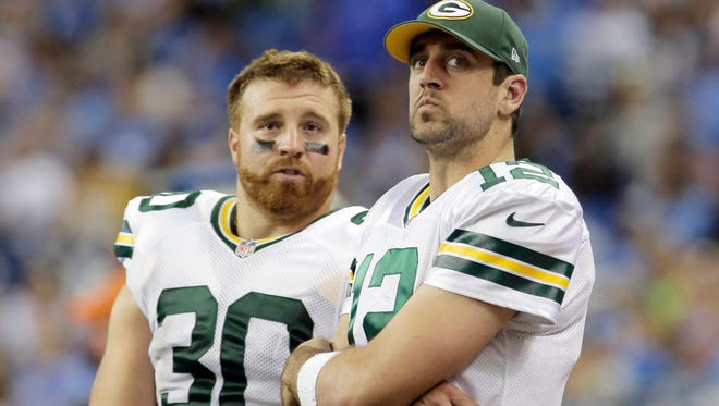 Green Bay Packers quarterback Aaron Rodgers (12) is seen on the sidelines with teammate John Kuhn on Sept. 21, 2014.