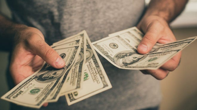 A man holding hundred-dollar bills.