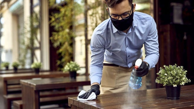 A waiter wearing a face mask and gloves cleans tables inside a restaurant.