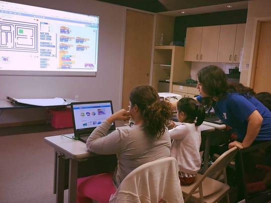 Christina Rosaria, assistant instructor, helps kids learn Scratch.