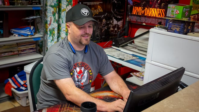 Zia Comics owner Troy Stegner in his office looks at Zia's eBay store which he uses to buy and sell comics and comic-related paraphernalia.