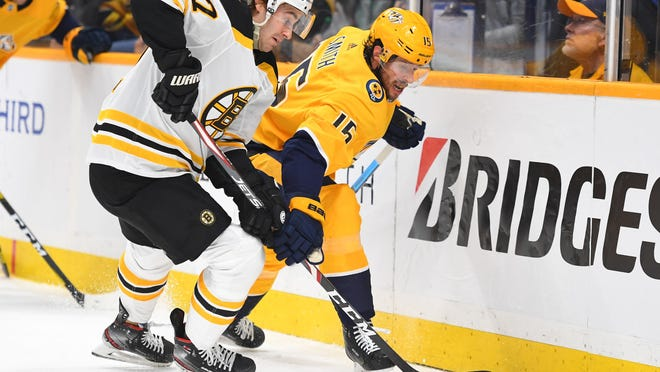 Predators winger Craig Smith battles Bruins defenseman John Moore during a game on Jan. 7. The two players will be teammates this coming season after Smith agreed to a two-year contract on Saturday.