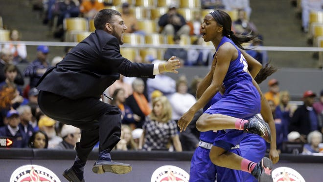 Tennessee State assistant coach Joe Bonham, left, celebrates with guard Brianna Lawrence during a timeout in overtime against Tennessee Martin in the OVC final.