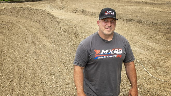 Dan Plourde walks on the motocross track he owns in Brookfield on Thursday.