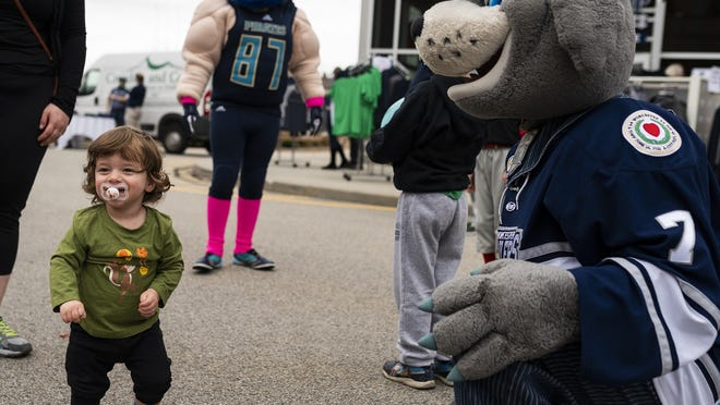 WORCESTER - The Worcester Railers hosted a Worcester sports teams sidewalk sale Saturday outside the Worcester Ice Center, where Jack Gable greets Railers mascot, Trax.