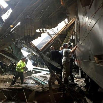 Train personel survey the NJ Transit train that crashed