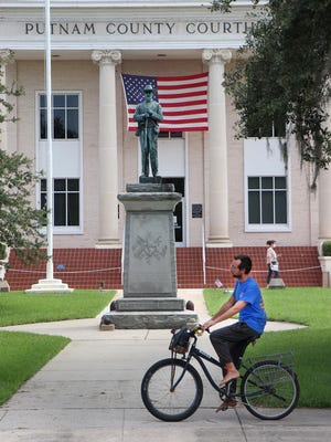 A bicyclist rides past the statue of a Confederate soldier in July on the grounds of the Putnam County Courthouse in Palatka. Advocates for the removal of the statue will hold a demonstration on Saturday at the courthouse.
