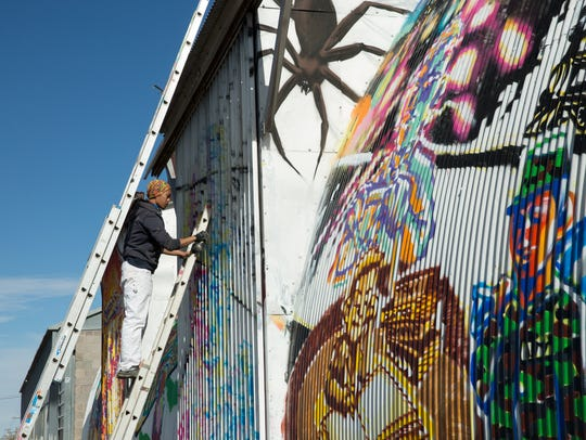 Yao Siao, a traveling artist works on a mural on the