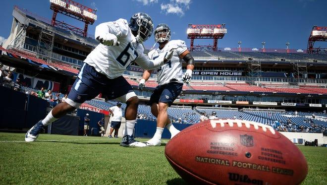 Titans guard Quinton Spain (67) and guard Josh Kline (64) warm up during a training camp practice at Nissan Stadium Saturday, Aug. 4, 2018, in Nashville, Tenn.