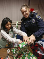 Adryana, 10, helps Manitowoc police officer Rebecca