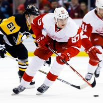 Red Wings center Tomas Nosek (83) skates with the puck chased by Penguins left wing Sergei Plotnikov (61) in the first period Thursday at Joe Louis Arena.