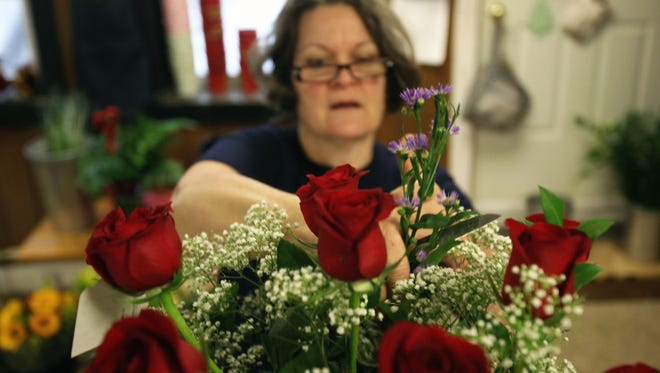 Jackie Cinaglia puts a flower arrangement together for Valentine's Day at Boyd's Flowers in Wilmington Wednesday, Feb. 12, 2014.