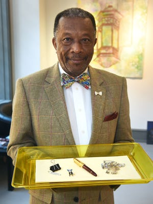 Henry Price displays his five necessary luxuries beginning with a set of cloths pins for emergencies, a George Rodrigue Blue Dog pin, paper clips, at least one fountain pen he keeps on hand at all times and his personal style statement of a bow tie.