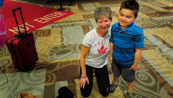 """Catie Sims, who lives in Canada and runs in honor of Garrett Sapp poses for a picture with Garrett after getting off a plane at the Nashville International Airport Friday Sept. 26, 2014, in Nashville, Tenn.  They met through the Facebook website """"I Run 4"""" and Sims is coming all the way from Canada to participate in a race this weekend for Garrett."""