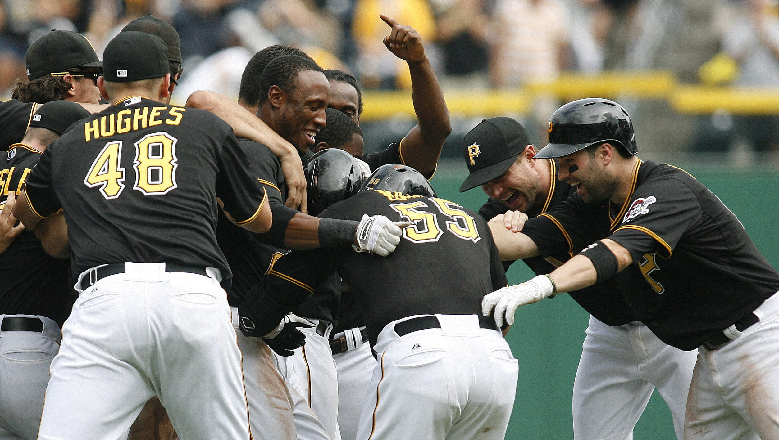 Aug. 8: Pirates catcher Russell Martin (center) is mobbed by teammates after driving in the game-winning run against the Marlins in the 10th inning.