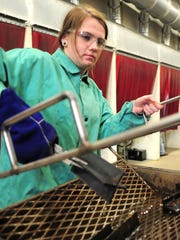 Butler Tech junior Megan Thompson cools off a welding project in a tank of water. She is one of many girls studying in its welding technology program.