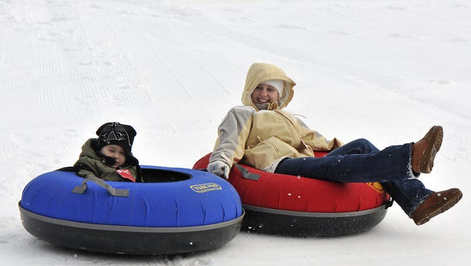Two people tube down a hill at Hawk Island in Lansing. Snow showers are expected in Lansing on Wednesday night.