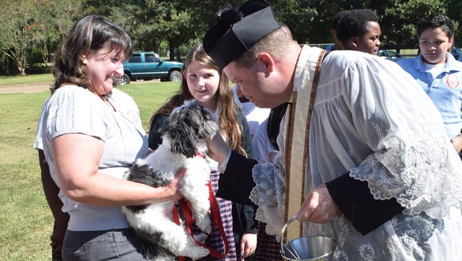 The Rev. Chad Partain (right), pastor of St. Frances Cabrini Church in Alexandria, blesses Oreo, the family pet of Racheal Erickson (left) and daughter Lilly Erickson (center). Lilly is a sixth-grader at St. Frances Cabrini School. Students brought family pets to be blessed Friday on the school grounds.