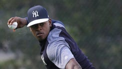 Luis Severino throws the ball to first as the pitchers