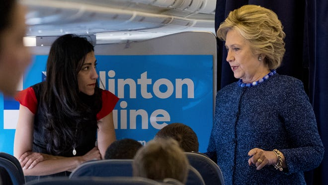 Democratic presidential candidate Hillary Clinton speaks with senior aide Huma Abedin aboard her campaign plane at Westchester County Airport in White Plains, N.Y., Friday, Oct. 28, 2016, before traveling to Iowa for rallies.