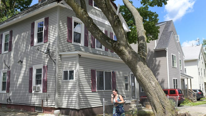 A woman walks by a large oak tree resting against a house at 38 Newbury St. Wednesday. It fell during the storm Tuesday.