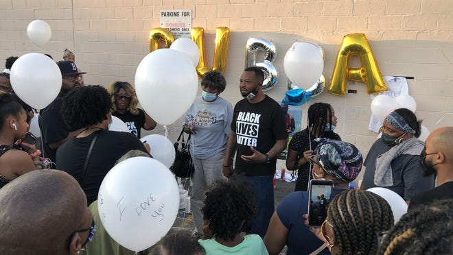 Mark Fisher, an organizer with Black Lives Matter, addresses a group of mourners in the parking lot on Broad Street where Delron Fields, 35, of Providence, was shot to death just after midnight on August 8.