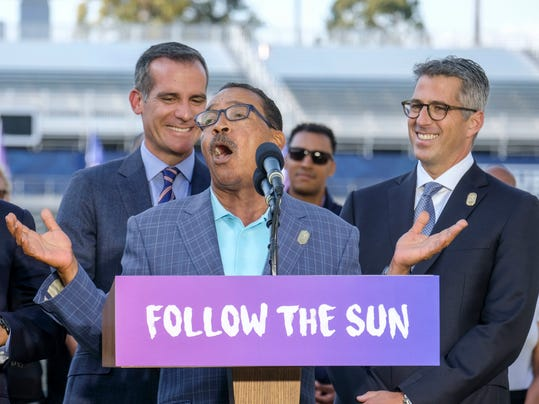 Los Angeles Mayor Eric Garcetti, left, and L.A. Olympic Committee leader Casey Wasserman, right, react as City Council President Herb Wesson speaks during a press conference to make an announcement for the city to host the Olympic Games and Paralympic Games 2028, at StudHub Center in Carson, outside of Los Angeles, Calif., Monday, July 31, 2017. (AP Photo/Ringo H.W. Chiu)