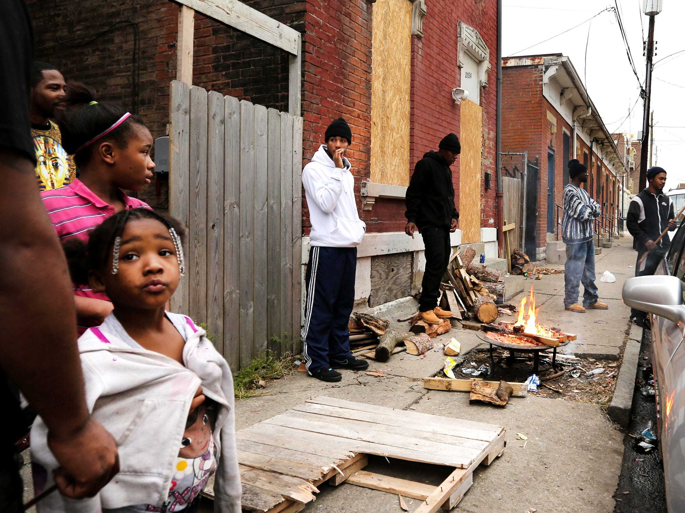 A make-shift fire pit keeps residents warm late in the day on Staebler Street in Lower Price Hill. The wood is donated and includes pieces leftover from construction projects in the area.