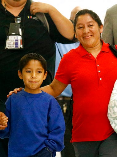 Darwin Micheal Mejia, 7, and his mother, Beata Mariana de Jesus Mejia-Mejia, are escorted to a news conference after their reunion at Baltimore-Washington International Thurgood Marshall Airport, June 22, 2018, in Linthicum, Maryland. The Justice Department agreed to release Mejia-Mejia's son after she sued the U.S. government in order to be reunited following their separation at the U.S. border. She has filed for political asylum in the U.S. following a trek from Guatemala.