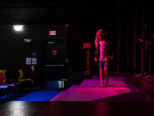 Charlotte Evans, 10, explores the stage of Rinehart
