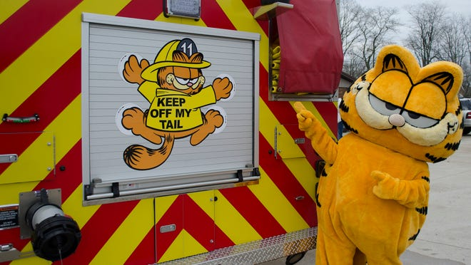 Garfield poses by the back of the Hamilton Township Volunteer Fire Company's new ladder truck, which features characters from the Garfield comic strip.