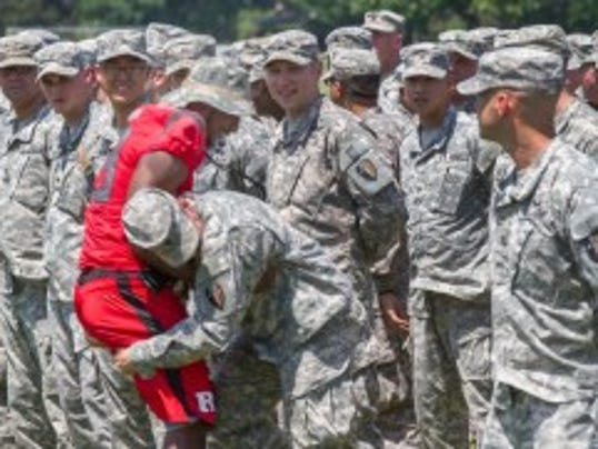 Specialist John Potenski of Mays Landing jokingly tries to test Rutgers halfback Savon Huggins to see exactly how tough he is as Huggins walks the rank shaking hands with the soldiers about to deploy.  (Pete Ackerman/MyCentralJersey.com)