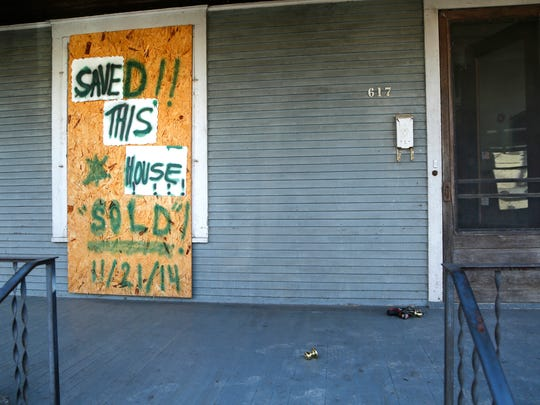 """A recently-modified sign on the front porch announces the good news, """"Saved!! This House Sold!"""" Wednesday, December 3, 2014, at 617 New York Street in Lafayette. The house which was once eyed by the city for demolition in the Ellsworth-Romig historic neighborhood has been sold."""