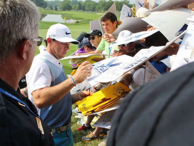 Rory McIlroy, currently ranked No.1 in the world, is swarmed by autograph seekers at the 18th green at Valhalla Wednesday morning. Aug. 6, 2014