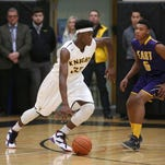McQuaid's Isaiah Stewart (left) drives to the basket during the team's win at home over Theodore Buckner (5) and his East High teammates.