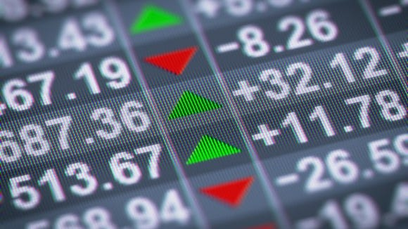 Stock market prices on an LED screen with green and red arrows indicating changes.