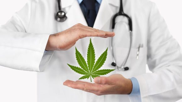 A physician holding a medical cannabis leaf between his hands.